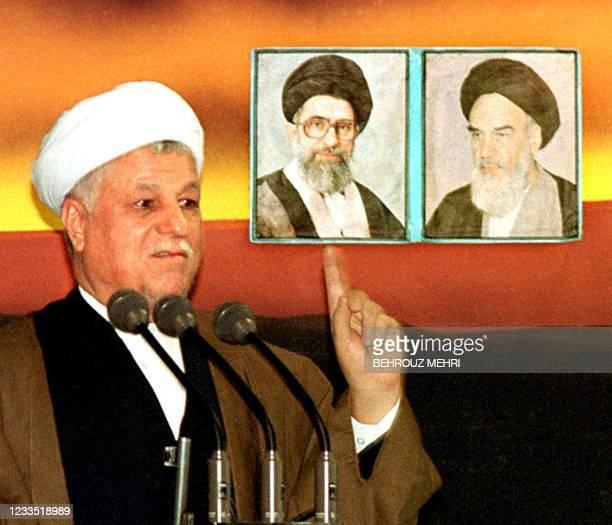 Former Iranian president Ali Akbar Hashemi Rafsanjani gestures, under a picture of late founder of the Islamic Revolution Ayatollah Ruhollah Khomeini...