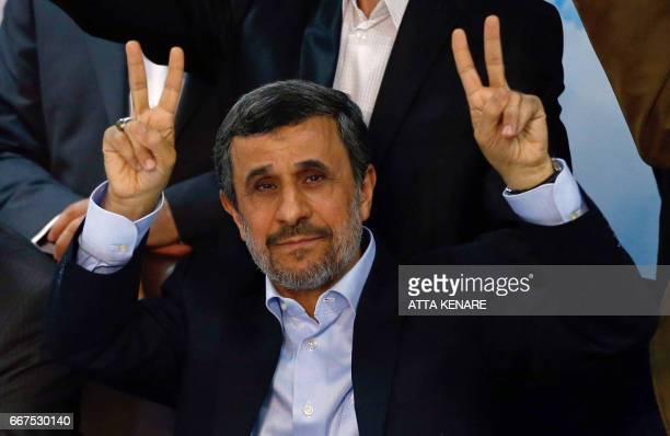 Former Iranian president Mahmoud Ahmadinejad flashes the sign for victory at the Interior Ministry's election headquarters as candidates begin to...