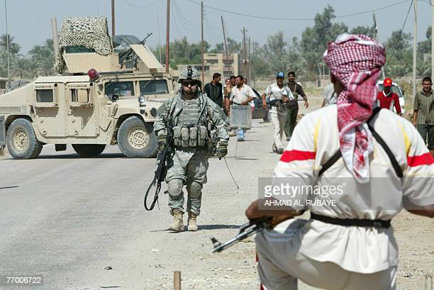 Former Iraqi insurgents , members of the Sunni Anbar Awakening, and US army soldiers, their former ennemies, guard a meeting between Sunni and Shiite...