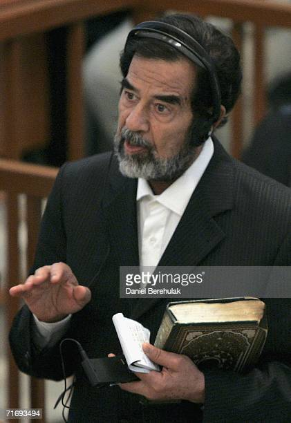 Former Iraqi President Saddam Hussein addresses the court holding the Koran during day 2 of the Anfal Capmpaign trial in Baghdad's heavily fortified...