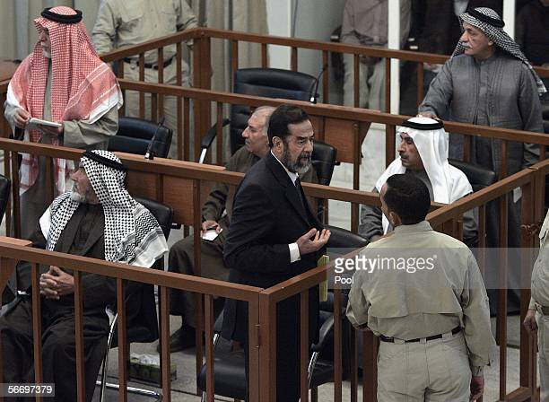 Former Iraqi President Saddam Hussein argues with a court guard after his half brother Barzan Ibrahim alTikriti was forcibly removed from their trial...