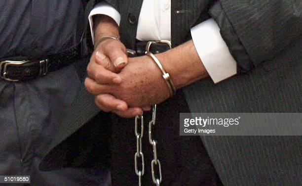 Former Iraqi President Saddam Hussein hands are seen in shackles prior to a July 1 2004 hearing in Baghdad Iraq to list the charges against him and...