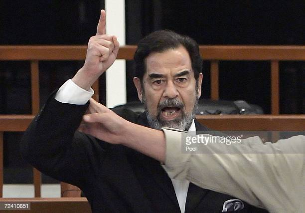 Former Iraqi President Saddam Hussein is held by a court bailiff during his trial in the fortified 'green zone' on November 5 2006 in Baghdad Iraq...