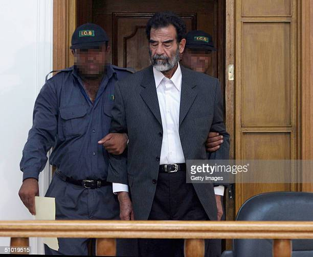 Former Iraqi President Saddam Hussein is lead by guards into an Iraqi courtroom on July 1 2004 in Baghdad Iraq to listen to a list of charges against...