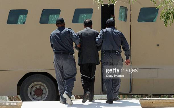 Former Iraqi President Saddam Hussein is lead in shackles away from an Iraqi courtroom July 1 2004 in Baghdad Iraq after hearing a list of charges...