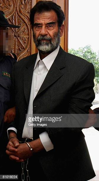 MILITARY**** Former Iraqi President Saddam Hussein is lead in shackles into an Iraqi courtroom July 1 2004 in Baghdad Iraq to listen to a list of...