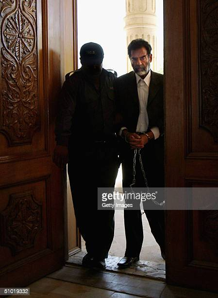 Former Iraqi President Saddam Hussein is lead in shackles into an Iraqi courtroom July 1 2004 in Baghdad Iraq to listen to a list of charges against...