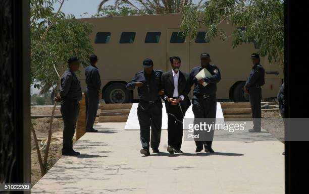 Former Iraqi President Saddam Hussein is lead in shackles into an Iraqi courtroom to listen to a list of charges against him and 11 of his top...