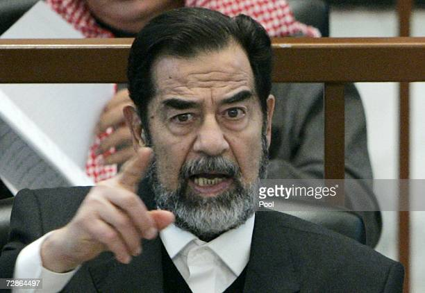 Former Iraqi President Saddam Hussein points while listening to the prosecution during his 'Anfal' genocide trial on December 21 2006 in Baghdad Iraq...