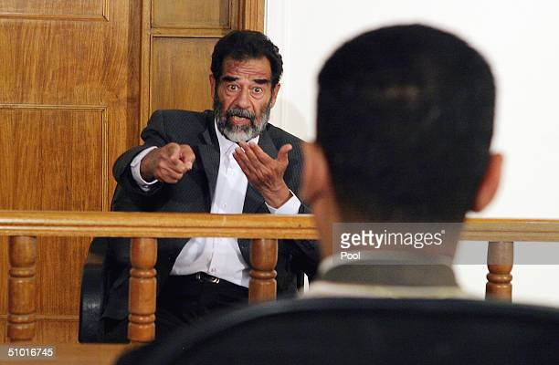 Former Iraqi President Saddam Hussein responds as a list of charges that he and 11 other high level defendents will face is read in an Iraqi...
