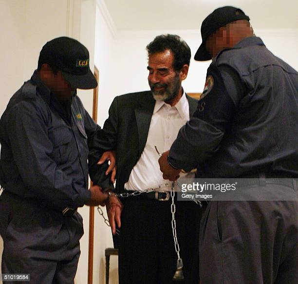 Former Iraqi President Saddam Hussein seen in shackles prior to a July 1 2004 hearing in Baghdad Iraq to list the charges against him and 11 of his...