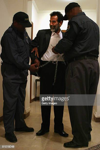 MILITARY**** Former Iraqi President Saddam Hussein smiles as two Iraqi guards remove his shackles before escorting him into an Iraqi courtroom July 1...