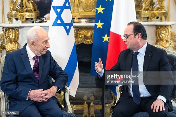 Former Israeli President Shimon Peres meets French President Francois Hollande during a meeting at the Elysee Palace in Paris, on March 25, 2016. /...