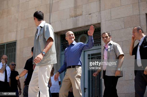 Former Israeli Prime Minister Ehud Olmert waves as he leaves the District Court after hearing the verdict in his trial on corruption charges...
