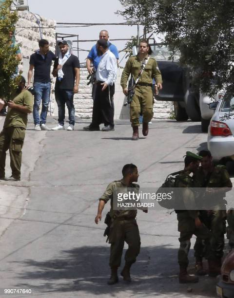 Former Israeli soldier Elor Azaria wears an Israeli national flag around his shoulders as he stands next to a man as he visits friends in the...