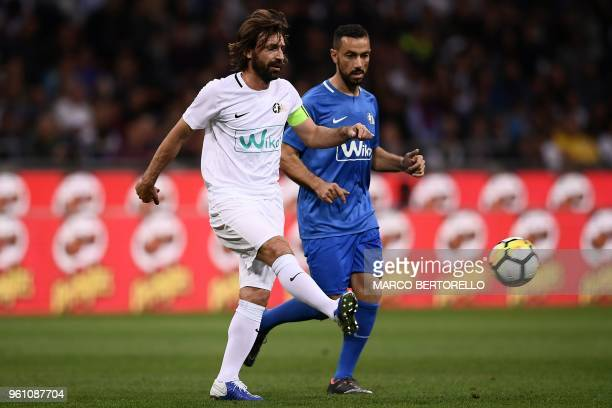 Former Italian football player Andrea Pirlo vies for the ball with Italian forward Fabio Quagliarella during the 'Notte del Maestro' a football match...