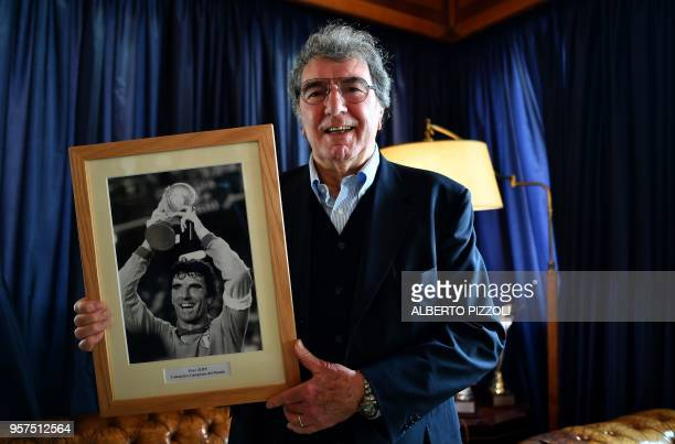TOUCHOT Former Italian goalkeeper and coach Dino Zoff poses with a picture of him holding the trophy of the Fifa football World Cup in 1982 during an...