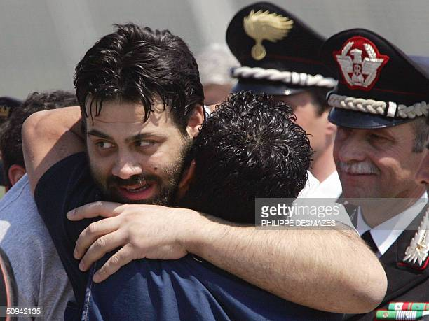 Former Italian hostage Maurizio Agliana is hugged by a friend 09 June 2004 as he arrives at Rome's Ciampino airport with two other Italian hostages...