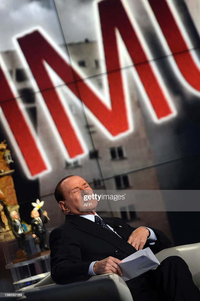 Former Italian Prime Minister Silvio Berlusconi reacts on the set of RAI 1 television programme 'Porta a Porta' on December 18, 2012 in Rome. Silvio Berlusconi the day before said a German-dominated Europe had imposed austerity on Italy as the three-time prime minister prepares for his sixth election campaign in two decades in politics. Flower reads 'No come back'.