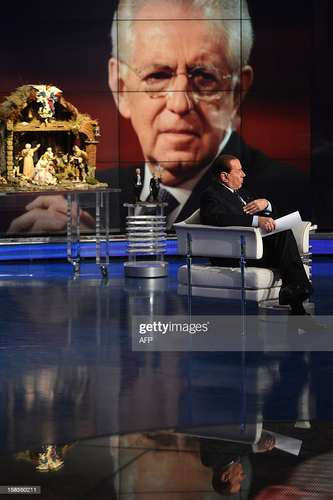 Former Italian Prime Minister Silvio Berlusconi reacts on the set of RAI 1 television programme 'Porta a Porta' with a portrait of current Prime Minister Mario Monti in the background on December 1...