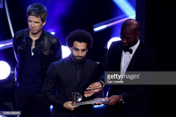 Former Ivorian footballer Didier Drogba and Noel Gallagher present Mohamed Salah of Liverpool with the trophy for the FIFA Puskas Award 2018 during...