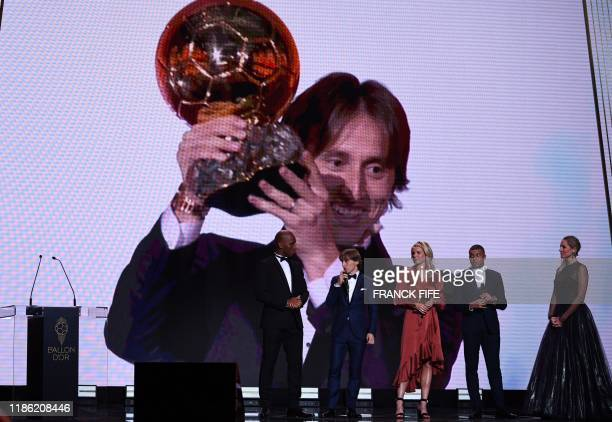 Former Ivorian forward Didier Drogba looks at former Ballon d'Or trophies laureates Real Madrid's Croatian midfielder and Ballon d'Or 2018 winner...
