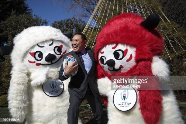 TOPSHOT Former Japanese football player Yasutaro Matsuki poses with mascots Ren and G during a photo session to unveil the official mascots of the...
