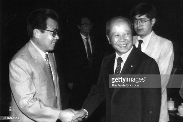 Former Japanese Prime Minister Kiichi Miyazawa shakes hands with CPC Politburo Standing Committee member Li Ruihuan during their meeting on July 27...