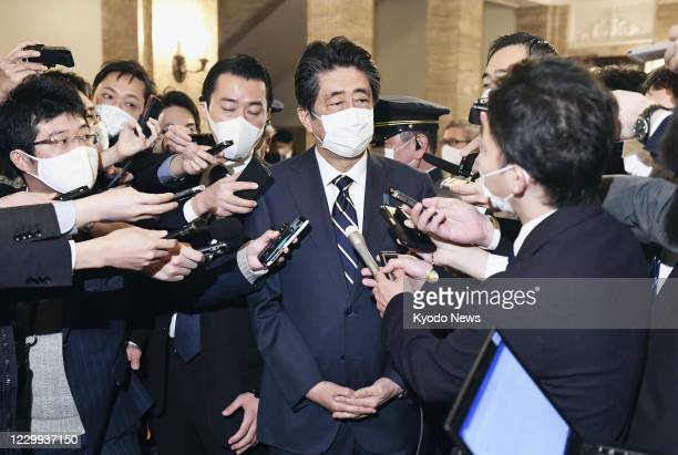 Former Japanese Prime Minister Shinzo Abe speaks to reporters after a House of Representatives plenary session in Tokyo on Dec. 4 amid allegations...