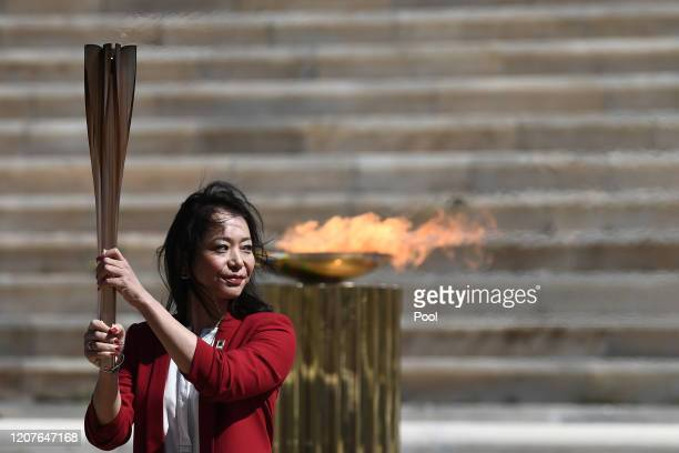 Former Japanese swimmer Imoto Naoko holds the Olympic torch during the Flame Handover Ceremony for the Tokyo 2020 Summer Olympics on March 19 2020 in...