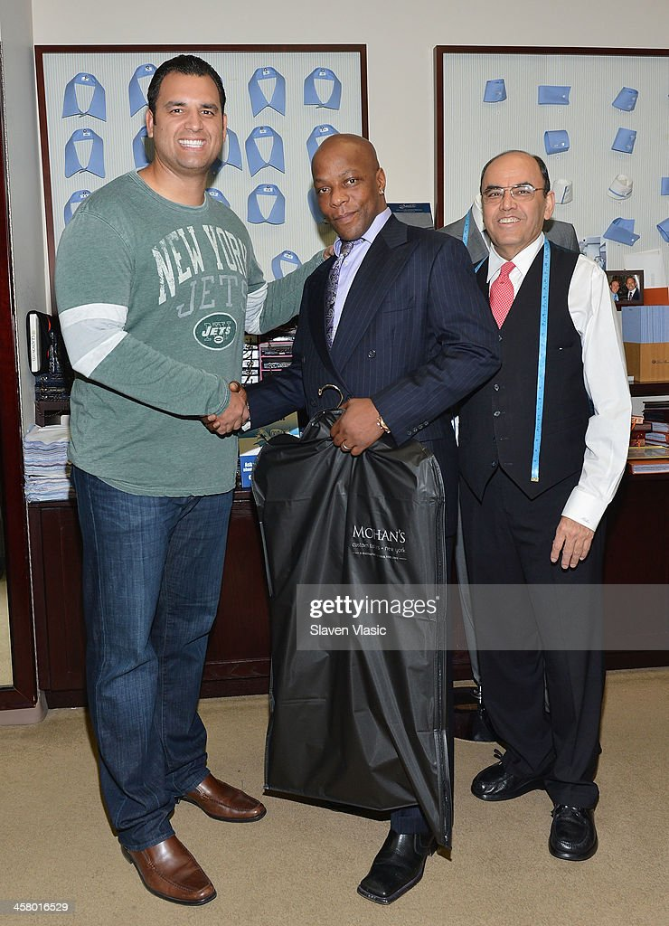 Former Jets player Anthony Becht, Doe Fund program member/recipient of a suit and Mohan Ramchandani attend the 2013 Mohan's Winter Coat Drive benefiting The Doe Fund at Mohan's Custum Tailors on December 19, 2013 in New York, United States.