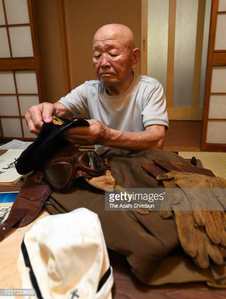 Former Kamikaze pilot Ryozo Kotoge looks at the old cap he used to wear when he was a member of the former Imperial Japanese Navy along with other...