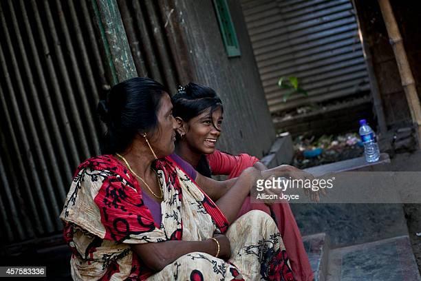 Former Kandapara brothel sex worker 50 year old Rekha sits with 13 year old Asthma Reyamoni on October 18 2014 in Tangail Bangladesh Rakha ran away...