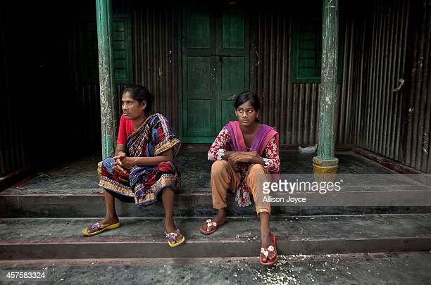Former Kandapara brothel sex workers 37 year old Parvin Shanti Akhter and her daughter 13 year old Asthma Reyamoni sit in front of their home on...