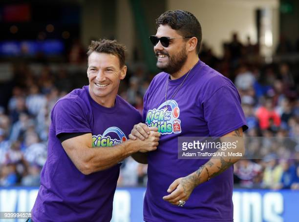Former Kangaroos legend Brent Harvey shakes hands with Dan Sultan kicking for the Saints as part of the kick for kids activation to raise money for...