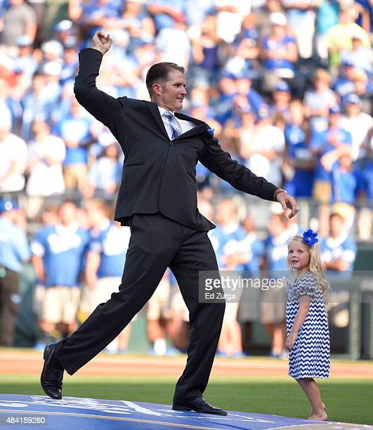 Former Kansas City Royals first baseman Mike Seeeney throws out the first pitch as he daughter Fiona looks on during his induction ceremony into the...