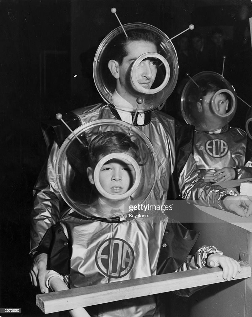 Former King Peter of Yugoslavia and his son Prince Alexander wearing space suits as they prepare to enter the 'Space Machine' at the Schoolboys' Own Exhibition, Horticultural Hall.