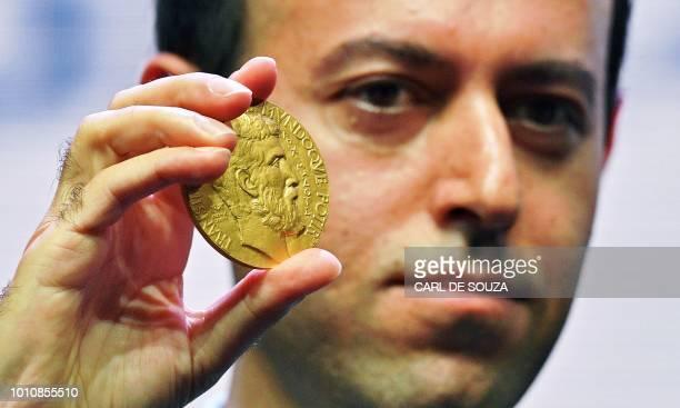 Former Kurdish refugee turned Cambridge University professor Caucher Birkar holds up a new Fields Medal for Mathematics presented to him in Rio de...