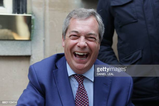 Former leader of the antiEU UK Independence Party Nigel Farage reacts after being congratulated outside a pub in Westminster in London on March 29...