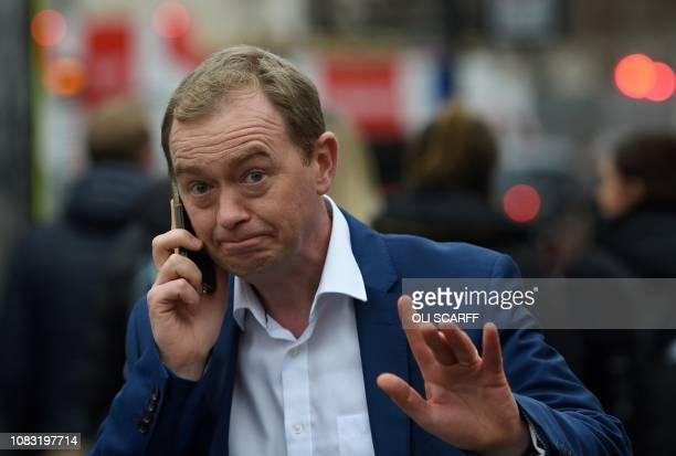 Former leader of the Britain's Liberal Democrats Tim Farron speaks on a mobile phone as he walks through Westminster in central London on January 16...