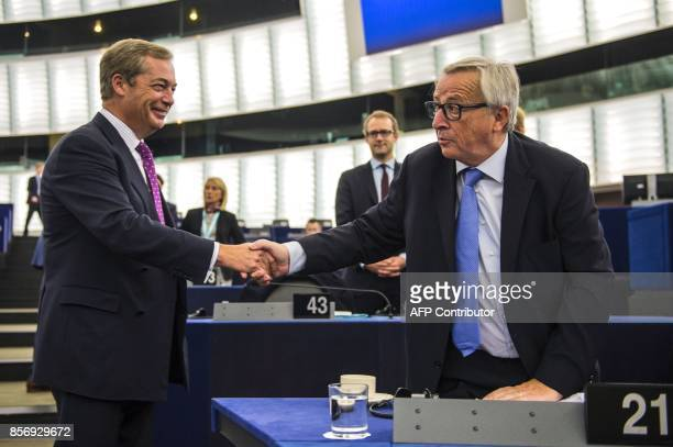 Former leader of UK Independence Party Nigel Farage shakes hands with European Commission President JeanClaude Juncker before a debate on the...