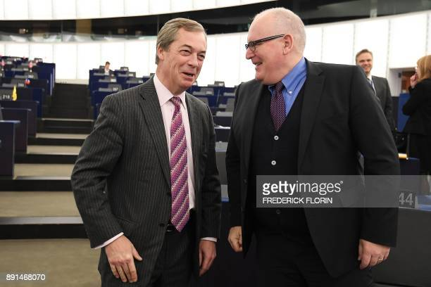 Former leader of UK Independence Party Nigel Farage speaks with First VicePresident of the European Commission Frans Timmerman prior to a debate on...