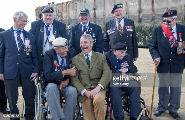 Former leader of UKIP Nigel Farage speaks with Veteran Harry Card who served on HMS Swift on DDay as he joins veterans on the beach at Arromanches as...