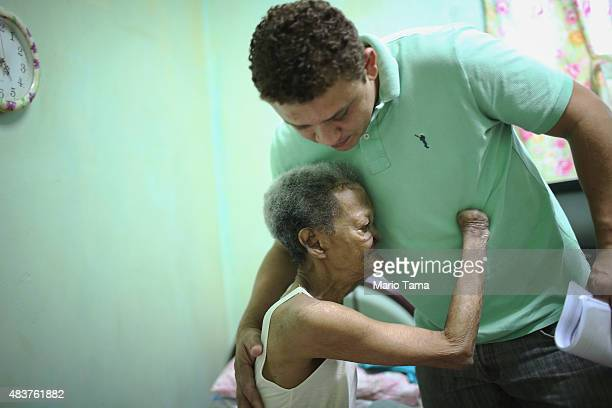 Former leprosy patient Tereza Alves dos Santos hugs a worker in her room in Hospital Curupaiti part of a former leprosy colony on June 10 2015 in the...