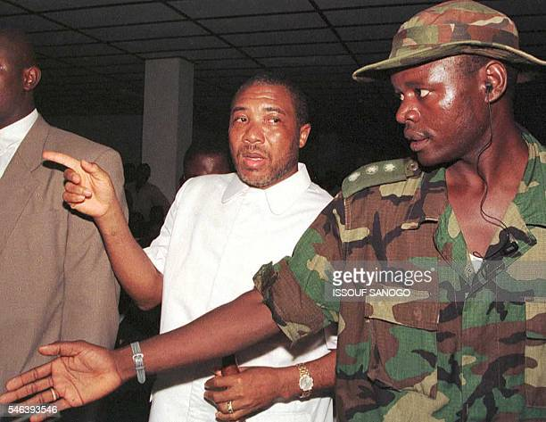 Former Liberian Warlord Charles Taylor is escorted by an ECOMOG soldier 24 July after his victory in the 19 July presidential elections was...