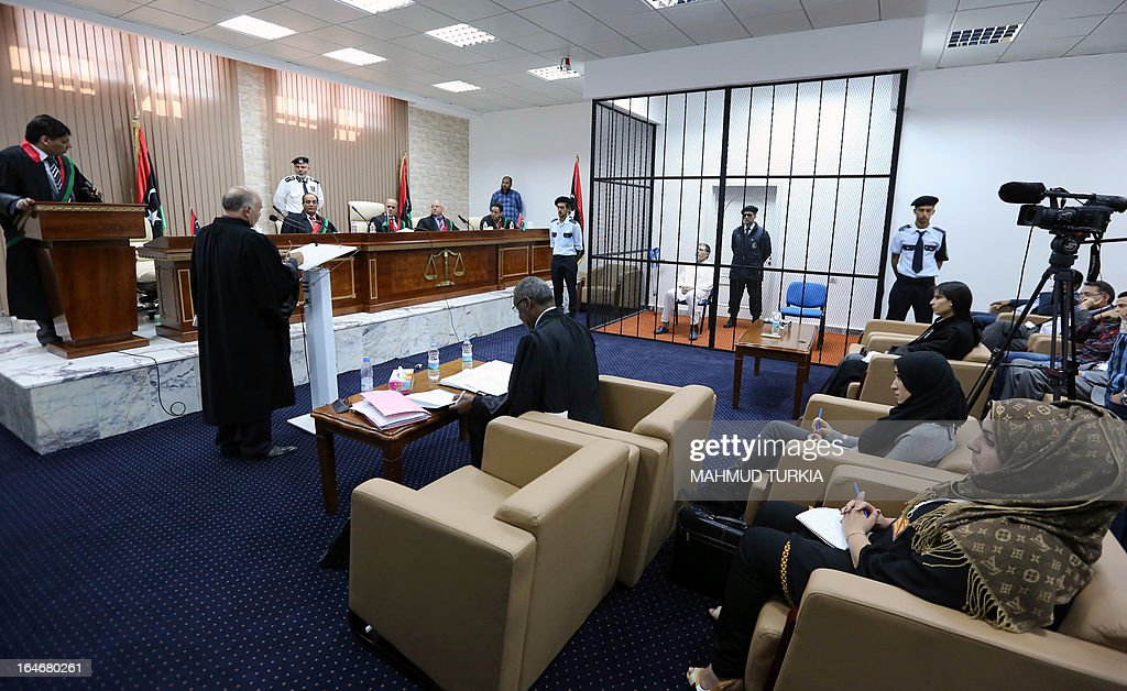 Former Libyan foreign intelligence chief Bouzid Dorda (C-back) sits behind bars during a hearing in his trial in Tripoli on March 26, 2013. The former foreign intelligence chief, the first of Moamer Kadhafi's top officials to face justice, is accused of ordering security forces to use live ammunition against demonstrators last year.