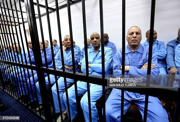 Former Libyan intelligence chief Abdullah al-Senussi sits dressed in prison blues with other defendants behind the bars of the accused cell during a...
