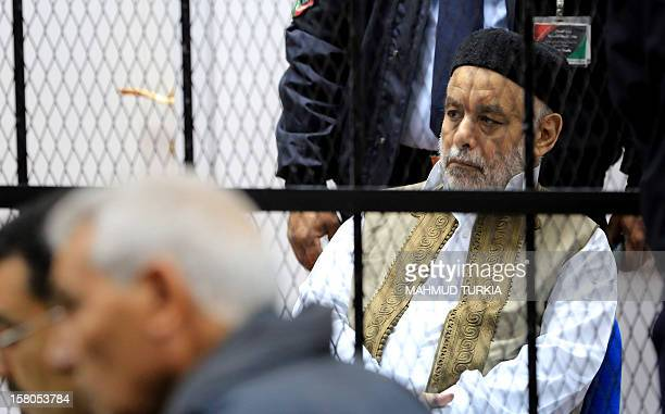Former Libyan prime minister Baghdadi alMahmudi sits behind bars during his trial at a courtroom in Tripoli on December 10 2012 The trial of Mahmudi...