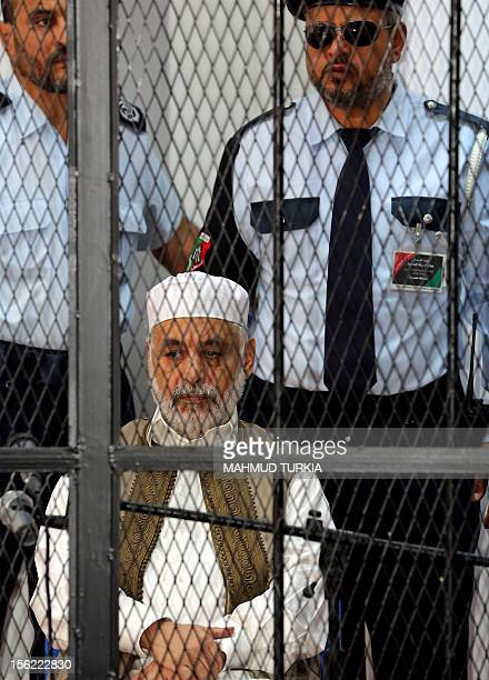 Former Libyan prime minister Baghdadi alMahmudi sits behind bars during the first hearing in his trial at a courtroom in Tripoli on November 12 2012...