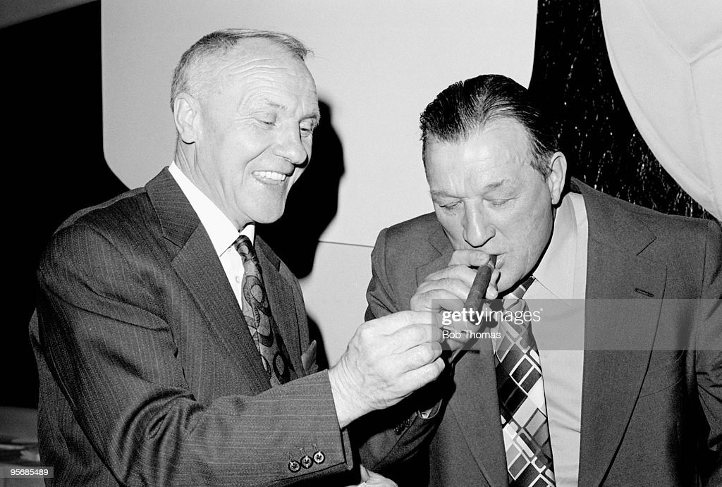 Former Liverpool manager Bill Shankly (left) lights a cigar for his successor Bob Paisley, who was named as the Football Manager of the Year at a lunch in Glasgow, 14th May 1976. Liverpool won the First Division Championship in the 1975-76 season.